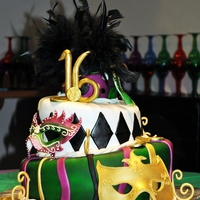 Mardi Gras 16Th Birthday Cake   All is edible except for the feathers on top and the foil for the coins:). Masks are made from MMF with butter cream details.