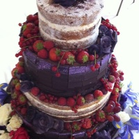 Wedding Cake Decorated With Chocolate Slabs Fruit And Sugar Flowers Wedding cake, decorated with chocolate slabs, fruit and sugar flowers.