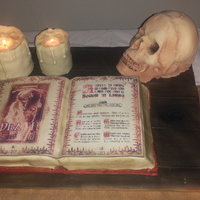Sorcerors Table Spellbook made from vanilla sponge, with vanilla sponge skull and chocolate sponge candles covered in white modelling chocolate. Cake board...