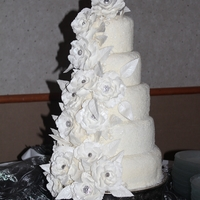 New Year's Eve Wedding Cake A winter wonderland covered in 14 pearl rose and leaves with bling centers, white cake covered in buttercream, topped with edible glitter...