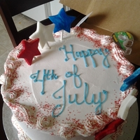 4Th Of July Red, white, and blue cake covered in whipped cream and decorated with fondant stars