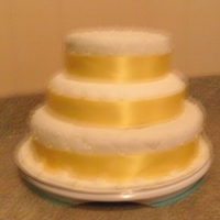 Quilted Chocolate cake with chocolate butter cream frosting, covered with white fondant with a quilted pattern. Yellow ribbon for accents