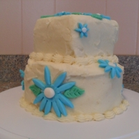 Blue Daisies Yellow cake with buttercream icing. Shelling around the bottom and blue fondant daisies.