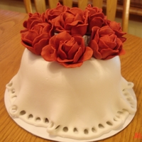 Roses On A Tablecloth Cake covered with MMF, and cut out circles at the bottom. Roses made of gumpaste.