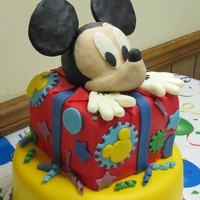 "Mickey Mouse Says ""surprise"" And Pops Out Of Present Mickey says ""Surprise!"" Cake covered with fondant. Mickey made out of rice crispy treats and covered with modeling chocolate. All..."