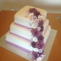 Purple Flower Cascade Cake This was my first wedding style cake for my husbands sister, was actually for her engagement party. All flowers are made from fondant