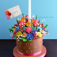 Floral Centerpiece Birthday Cake Cacao Noir Chocolate Cake iced in Chocolate Swiss Meringue Buttercream is topped with an array of fondant and royal icing flowers.