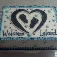 Blue And Black Baby Shower Cake Double layer 9x13 cake. White with buttercream icing and FBCT heart and footprints on top.