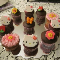 Hello Kitty Cupcakes With Flowers 3 different flavor,chocolate,red velvet and strawberry cupcakes with fondant flowers