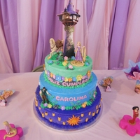 Tangled Buttercream covered cake. Decorations are gumpaste and fondant. Figurines are toys and the tower is made of styrofoam.
