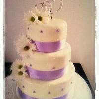 June Wedding Three tier fondant cake, with light purple pearl accents. Fresh flowers along the side