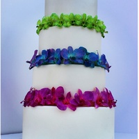 Vibrant Orchids Vibrant orchid surround the tiers of this pearl luster 4 tier wedding cake