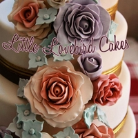 Vintage Rose a marbled ivory tiered cake with a cascade of large sugar roses in vintage hues to give an antique feel