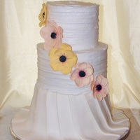 I wanted to try something different (for me) so i did the top two tiers in BC and Fondant draping on the third. Hand made gumpaste flowers...