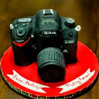 "Nikon Camera Cake With Zoom carved from an 8"" white cake,"