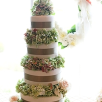 "Height And Hydrangea Four tiers of cake, stacked with about 4"" of space in between, ribboned and filled with fresh antique green hydrangea. Very simple but..."