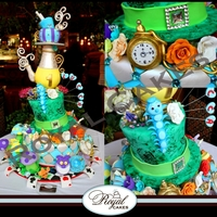 The Wonderful World Of Alice!   A stunning Alice in Wonderland cake featuring teacups, characters, mushrooms, sugar flowers, and Alice herself as the cake topper!