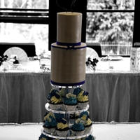 Elegant Wedding Cupcake Tower   A tall skinny two tier cake atop a tower of cupcakes with fondant hearts stamped with the couple's initials.