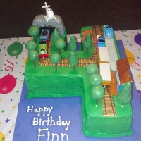 Thomas The Train My son asked for a thomas cake. This is what I came up with. Cake is in the shape of a 4. The trees are cake pops. The tunnel and station...