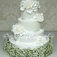 "White Roses Wedding Cake An all white wedding cake with sugar roses and hydrangea petals. It's sitting on top of a fresh gypsophila ""cake stand""."