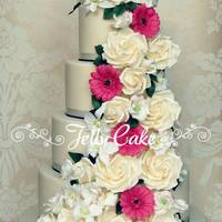 Floral Cascade Wedding Cake A 4 tier cake decorated with a cascade of sugar roses, Singapore orchids, lisianthus and germini's to match the brides bouquet.