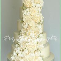 Ivory Rose Cascade Wedding Cake Lots of ivory sugar roses, hydrangeas and a peony to match the wedding flowers.