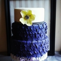 Purple Ruffle Wedding Cake   Bottom tiers are covered in purple ruffled petals and the top tier is trimmed with a studded ribbon and adorned with a soft green flower.