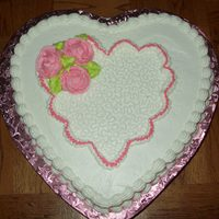 This Is A Lemon Heart Shaped Cake With Classic Buttercream Icing Its Decorated With Cornelli Lace And Roses Made Out Of Decorators Icing This is a lemon heart shaped cake with classic buttercream icing, its decorated with cornelli lace and roses made out of decorators icing...