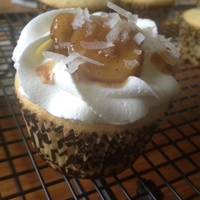 Banana's Foster Cupcake A coconut cake topped with Bananas foster sauce and bananas and a whipped cream topping.