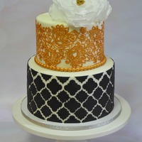 Black And Gold Cake An anniversary cake in black and gold. The top tier is edible lace and topped with wafer paper.