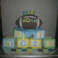 "Baby Blocks With Football Baby Shower Cake 6 individual ""baby blocks"" cakes and a Football cake on top with fondant baby blankie"