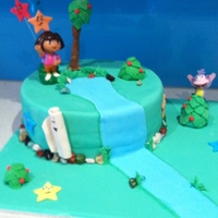 Dora Cake Dora cake requested (plastic dora and the monkey supplied by recipient). Fondant covered, chocolate rocks, all other decorations fondant....