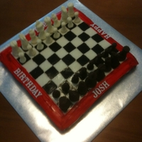 Chess Board 100% edible chess set cake. The pieces are molded chocolate and the cake covered in chocolate icing and fondant strips