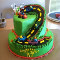 Race Track Cake Cake made for 2 year old boy. Client asked for NO Fondant! So, cars and cones are molding chocolate candies. Everything else is buttercream...