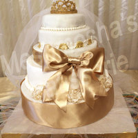 White And Golden Wedding Cake Chocolate cakes covered in white fondant and decorated with golden satin ribbon, golden satin bow, gumpaste tiara, pearls, and gold-rimmed...