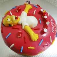 Homer Simpson Homer Simpson lying on a glazed donut ... while sipping beer. The figure is made of fondant and Homer is hollow belly (to save fondant and...