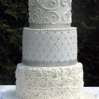 3 Tier All White Wedding Cake Decorated With Buttercream Rosettes Quilting And Scrolling And Accented With Silver Pearls And Glam Ribbon 3-tier all-white wedding cake decorated with buttercream rosettes, quilting and scrolling, and accented with silver pearls and glam ribbon...