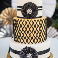 Black White And Gold Wedding Cake Incorporating The Paper Wheels And Some Bling With A Quatrefoil Center Tier Black, white, and gold wedding cake incorporating the paper wheels and some bling with a quatrefoil center tier.