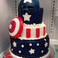 Captain America Capt. America cake was covered in MM fondant. Mask and shield were made out of gumpaste.