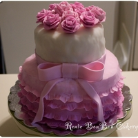 Flowers & Frills Two tier fondant covered cake with rose cluster topper, bow, and frills