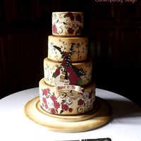 Love Rocks Guitar and tattoo-themed wedding cake. Hand painted rose and vine tattoo details, vintage colour effect and bride and groom crossed guitars...