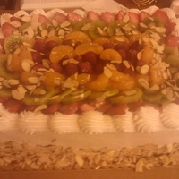Rasberry Cake With Fresh Fruits. Raspberry filling, fresh fruit, almonds with a whipped frosting.