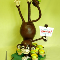 3D Gravity Defying Monkey Birthday Cake 3D Sculpted Monkey doing a handstand. Coated in ganache then covered and decorated in modeling chocolate. His head and body are cake, as...