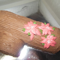 Holiday Yule Log Filled With Vanilla Cream Topped With Chocolate Buttercream And Three Pointsettias Holiday yule log filled with vanilla cream, topped with chocolate buttercream and three pointsettias