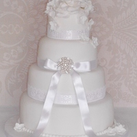 White Romantic Wedding Cake 4 tier white romantic wedding cake. lace ribbon with diamante broach and sugar roses.