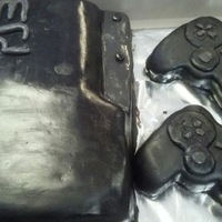 Ps3 Theme   Cake made to resemble Playstation 3 with controllers. The cake is chocolate decorated in mmf. Fun, fun cake to make.
