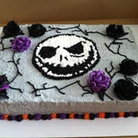 Jack Skellington Cake Halloween cake made during beginner cake class, practicing roses. Base frosting is Marshmallow buttercream tinted grey to look like stone....