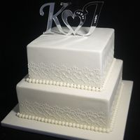 "Kirsty's Wedding Cake  Two tier (8"" 10"") white chocolate mud cake, layered with white chocolate ganache, covered in fondant. Royal icing stencilling..."