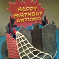 Spider Man Birthday Cake This cake is covered in fondant, and the building fronts and sign are a gumpaste/fondant mix.