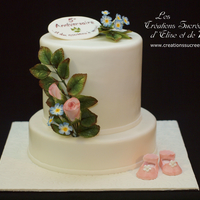 Wedding Anniversary And Baby Shower Cake White wedding anniversary cake with baby girl shoes to announce great news. Sugar flowers (roses and myosotis inspired filling flowers)....